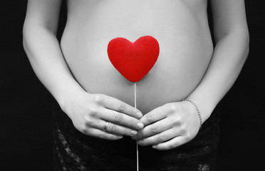 A pregnant woman holds her stomach at the red heart, she loves and is waiting for her future baby