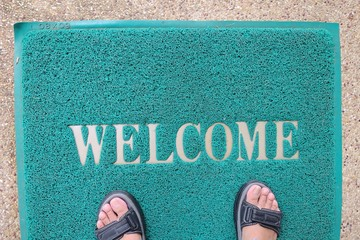A Welcome doormat with the feet with multipurpose shoes.
