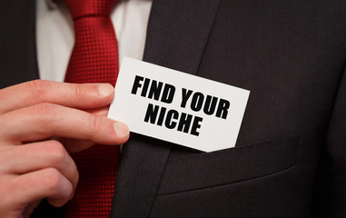 Businessman putting a card with text FIND YOUR NICHE in the pocket