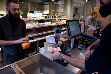 A shop holder receives cash from a customer in Brussels