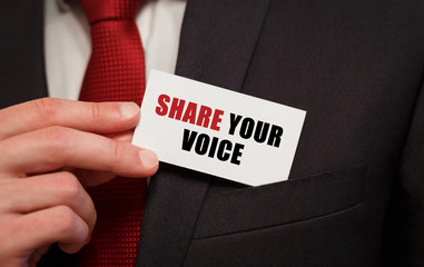 Businessman putting a card with text SHARE YOUR VOICE in the pocket