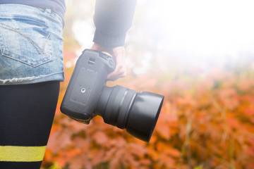 professional camera in girl's hand. photosession on a background of bright autumn landscape
