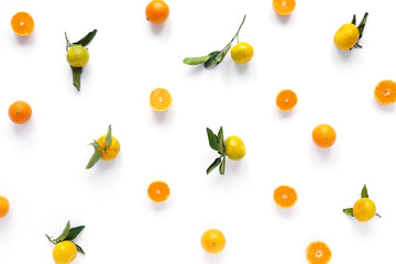 Food pattern of fresh fruit in a cut. Tangerines with green leaves. Composition from fruits, top view, flat lay. Citrus fruits background, wallpaper.