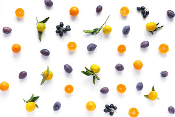 Food pattern of fresh fruit in a cut. Mandarins, black grapes, plums, tangerines with green leaves. Composition from fruits, top view, flat lay. Citrus fruits background, wallpaper.