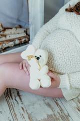 Pregnant woman holding a Teddy bear