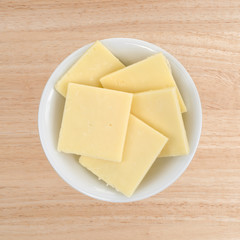 Top view of a small white bowl filled with sharp cheddar cheese square slices on a wood table.