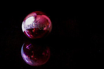 Christmas tree toy, a red ball, reflected on a black background.