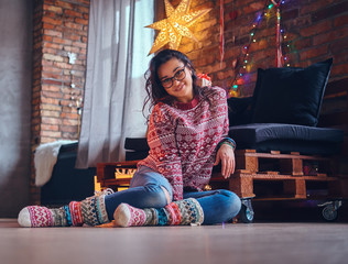 Brunette female in a room with Christmas decoration.