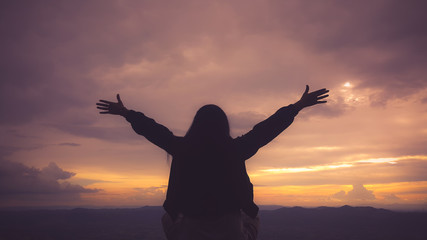 Silhouette freedom woman rise hands up to welcome a good day , open arms motivate enjoy and success the wish