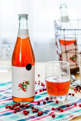 Bottle with Lingonberry Lemonade on Wooden Background, Vertical View