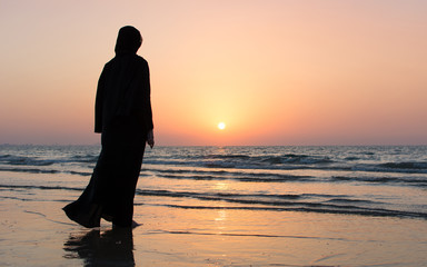 Woman in hijab standing on the beach