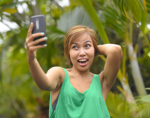 young sweet and pretty Asian woman holding mobile phone taking selfie picture in tropical jungle smiling happy posing cool in social media self portrait