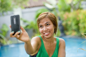 happy Asian woman taking selfie picture for social media internet app on mobile phone camera relaxed at resort swimming pool