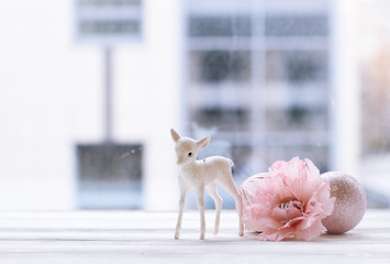Christmas decoration, artificial flower and balls and figurine of fawn against window
