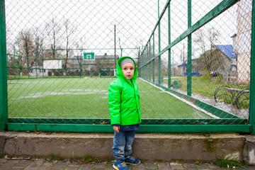 A boy stands near the football field.