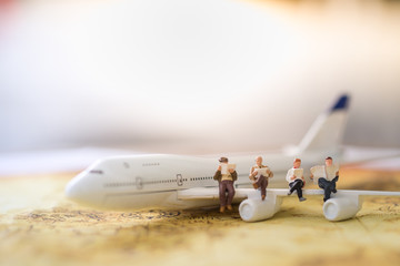 Travel and transportation Concept. Group of miniature figures sitting on wing of airplane and reading a book and newspaper on world map.