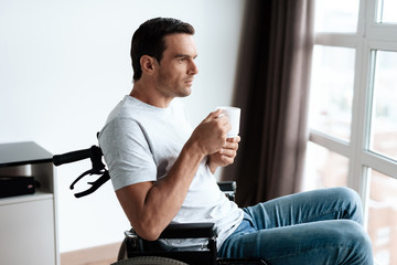A disabled person in a wheelchair sits in front of a large panoramic window and drinks coffee. He has a cup of coffee in his hand. He sits in the living room of his large modern apartment.