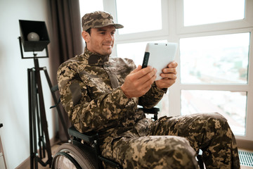 The disabled in military uniform sits in a wheelchair and communicates with someone through a tablet. He sits at a large panoramic window in his large modern apartment.
