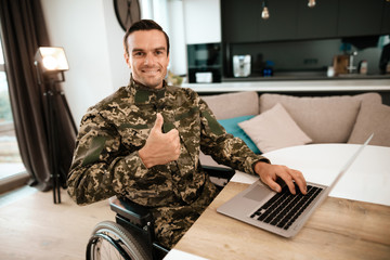 Disabled in military uniform, he sits next to his laptop and shows a thumbs-up. He sits at his desk. He is in his large modern apartment.