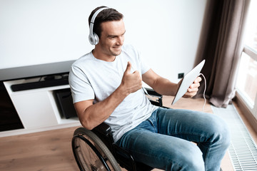 A disabled person in a wheelchair sits in front of a large panoramic window and communicates via video through his tablet. He has headphones on his head. He is in his large modern apartment.