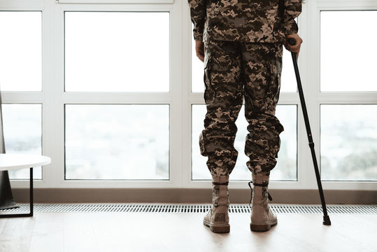 Close up. A disabled soldier is leaning on a crutch by the window. He looks into the large panoramic window. From the window you can see a beautiful view of the city.