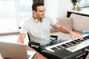 The disabled person is sitting in a wheelchair in front of the synthesizer. writes music. Nearby is his gray laptop. He is in his large bright living room. He enjoys music.