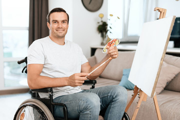 The disabled person is sitting in a wheelchair opposite the easel. He draws a picture. He is in his large bright living room. He smiles.