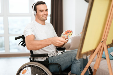 The disabled person is sitting in a wheelchair opposite the easel. He draws a picture. He is in his large bright living room. He is listening to music.