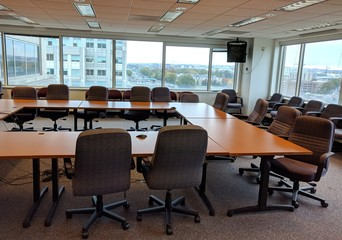 Empty meeting room with large windows overlooking city streets and buildings.