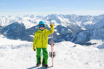 Smiling skier boy in the mountains on a sunny day. Ski,Sun, Snow and Fun.