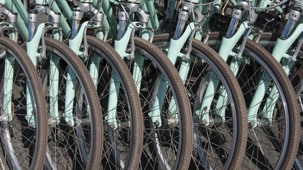 Abstract scene created by close-up, cropped bicycles, lined up in a symmetrical pattern, urban symbol for environmentally friendly means of transportation
