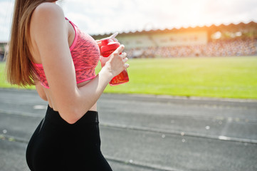 Fitness sporty girl in sportswear at stadium outdoor sports. Happy sexy woman with sport bottle mockup.