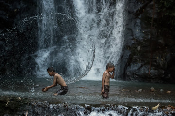 Two children playing water in the river at countryside Thailand.