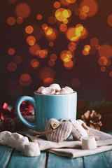 Blue mug filled with hot chocolate with marshmallow candies. Lights on background