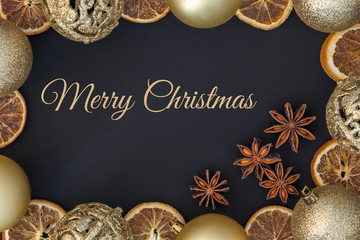Christmas card with gold baubles, dried orange and anise
