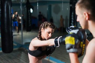 Young fighter boxer fit girl wearing boxing gloves in training  with  personal trainer in gym. Low key image. Woman power
