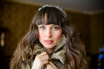 Home cosiness. Beautiful surprised fashionable woman at home in a winter jacket with jewelery on her head. portrait of a woman