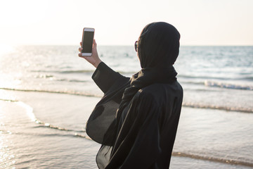 Woman in hijab taking picture on the beach