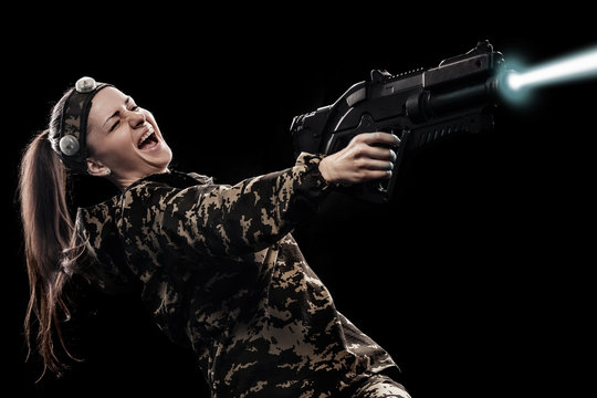 Heavily armed masked soldier isolated on black background. Paint ball and laser tag sport games.