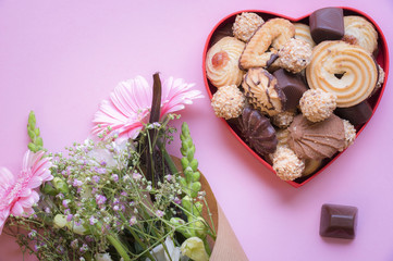 Heart shaped box with cookies and flowers - Gifting theme image with a red heart shaped box full of delicious sweets and a bouquet of flowers on a pink background. A greeting card idea.