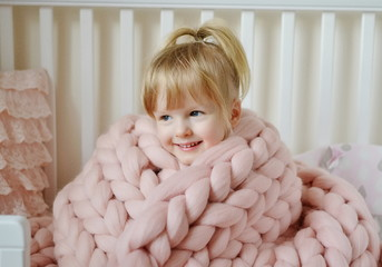Beautiful Little Happy Blond Ginger Girl Sitting on Bed with a Pink Knitted Giant Plaid