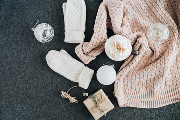 Women's winter clothes look on grey plaid. Warm beige sweater and white knitted mittens, gift box and glass balls. Christmas fashion composition. Flat lay, top view.