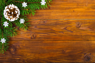Christmas wooden background with fir-tree and cones top view.