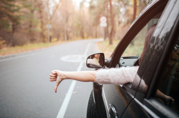 Female traveler on the road holding thumb down. Fall vacation, holidays, travel, road trip and people concept