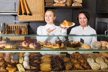 Friendly women with desserts in the pastry shop
