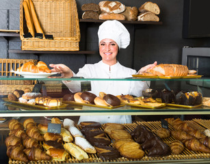 Woman offering deserts in the pastry shop .