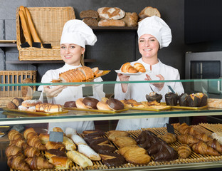 Glad woman and young girl reccomending pastry