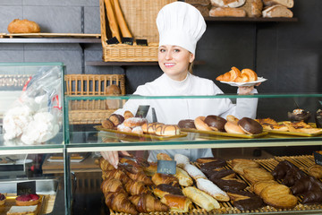 Girl offering desserts in the pastry shop .