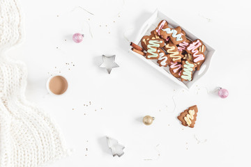 Christmas composition. Christmas gingerbread cookies, cup of coffee, knitted blanket on white background. Flat lay, top view