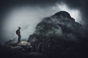 Mountain climber and dark, ominous, stormy view Wall mural